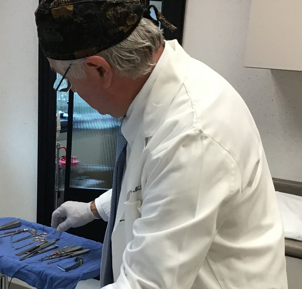 craig r dufresne md facs surgeon reaching for instruments in background